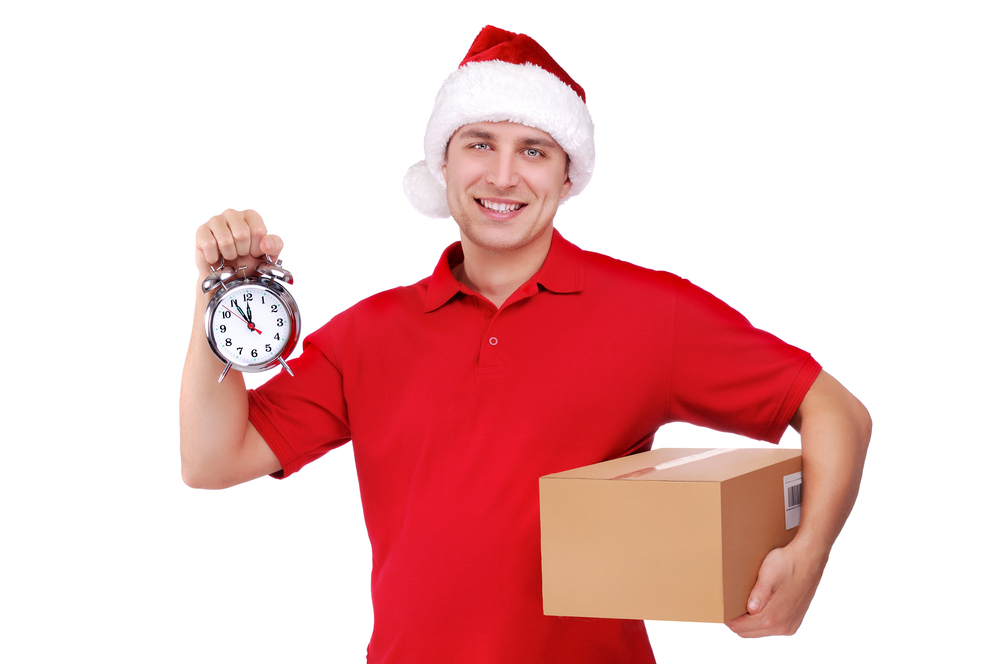 man wearing a Christmas hat with parcel and alarm clock